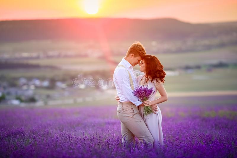 A loving couple standing in a lavender field and hugging. Beautiful bride dressed in luxurious wedding dress. Bride and royalty free stock photo