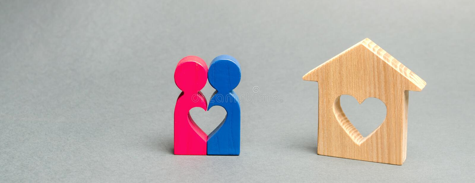 A loving couple is standing near a wooden house. The concept of finding a house or apartment for a young family. Affordable royalty free stock images