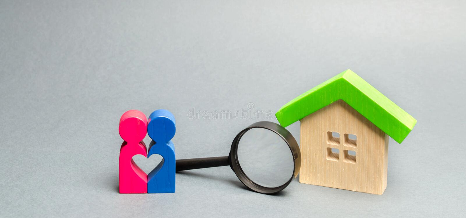 A loving couple is standing near a wooden house. The concept of finding a house or apartment for a young family. Affordable royalty free stock photography