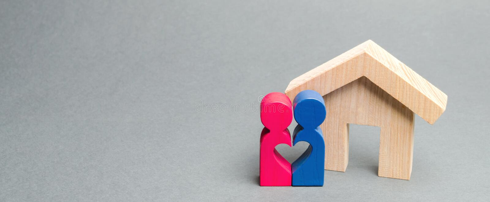 A loving couple is standing near a wooden house. The concept of finding a house or apartment for a young family. Affordable stock photos