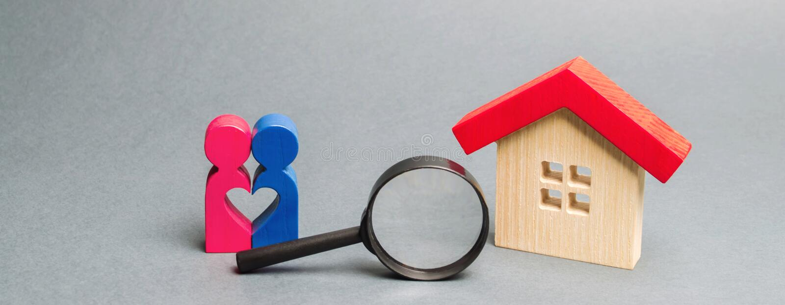 A loving couple is standing near a wooden house. The concept of finding a house or apartment for a young family. Affordable stock photo