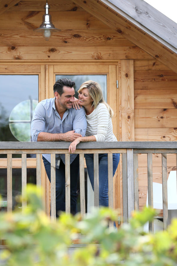 Loving couple standing on wooden house's terrace. Couple standing in log cabin terrace royalty free stock photography