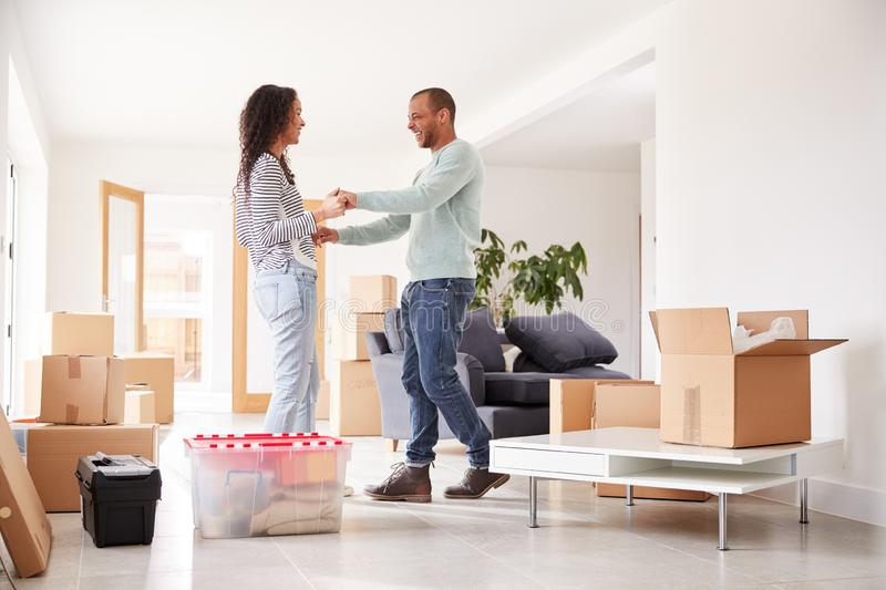 Loving Couple Surrounded By Boxes In New Home On Moving Day royalty free stock photos