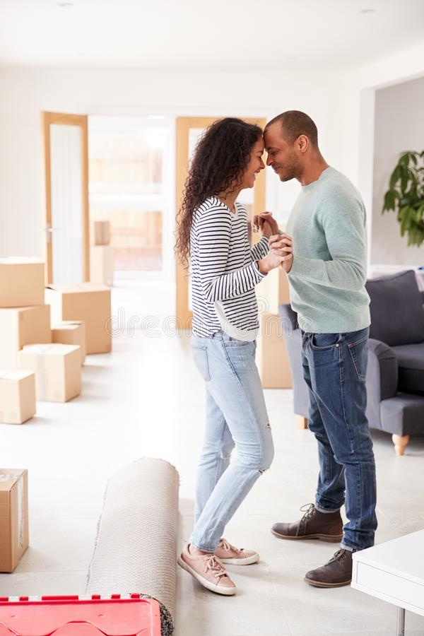 Loving Couple Surrounded By Boxes In New Home On Moving Day stock image