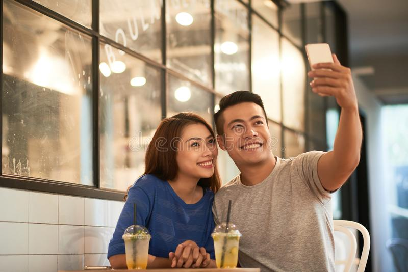 Loving couple taking selfie in cafe royalty free stock photo
