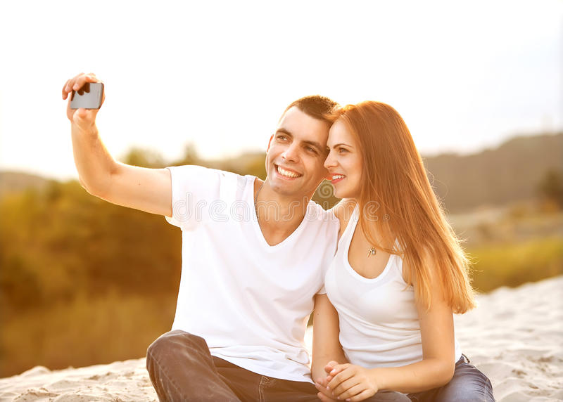 Loving couple taking selfie in the park royalty free stock photos