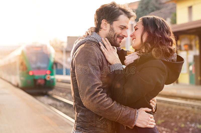 Loving couple at train station. Happy couple embracing on railway station platform stock images
