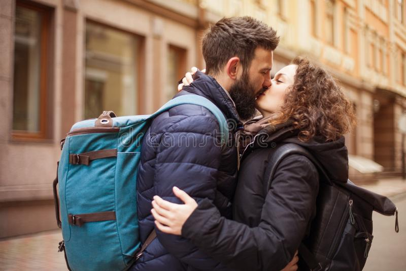 A loving couple of travelers with backpacks kissing outdoors in the old town - Concept of people and love stock photography