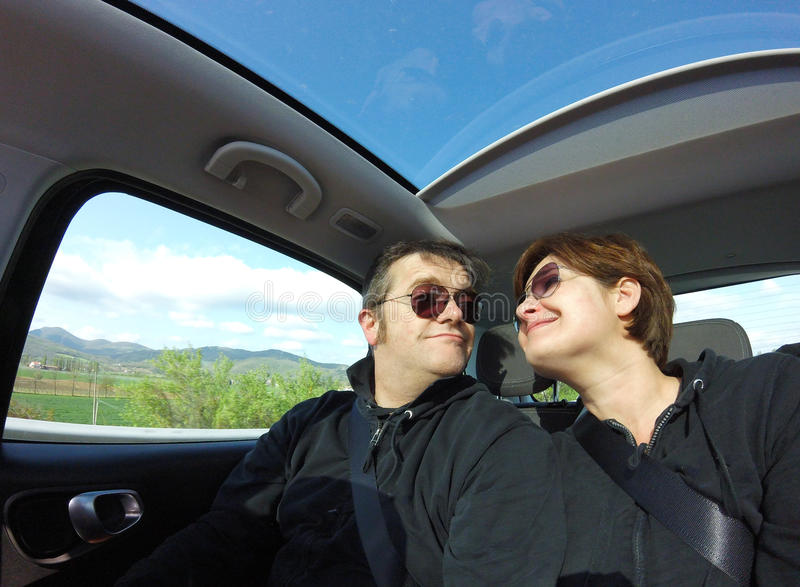 Loving couple traveling by car with panoramic roof. royalty free stock photo