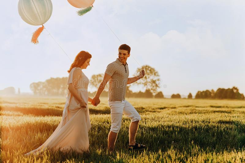 Loving couple walking in the field with helium colored balls stock photography
