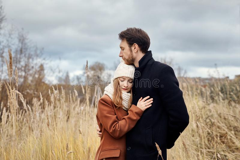 Loving couple walking in Park in autumn hugs and kisses. Autumn stock photography