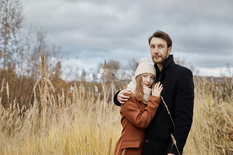 Loving couple walks in the autumn Park, hugs and kisses. Woman i stock images