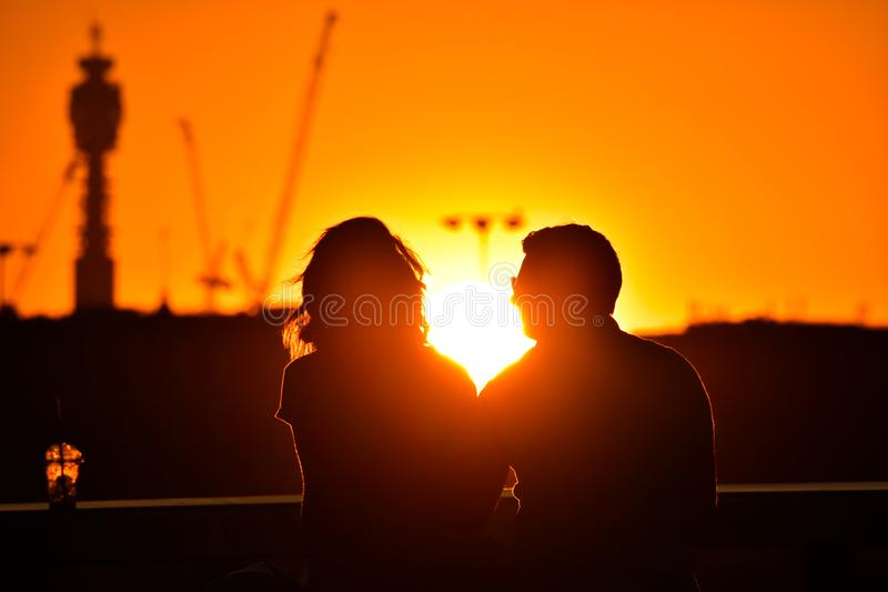 loving couple watching beautiful bright romantic sunset, sitting leaning against blue sport car. The fields around them. The youn stock photography