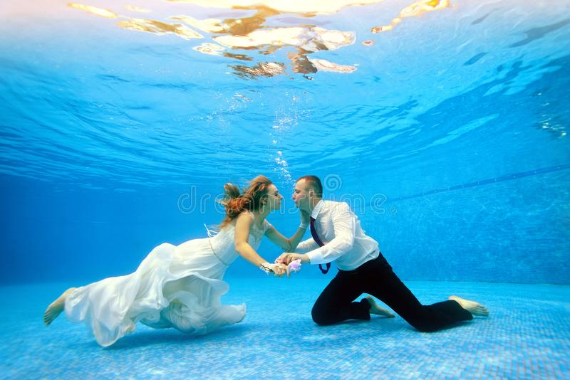 Loving couple in wedding dress swims underwater in the pool to meet each other royalty free stock photos