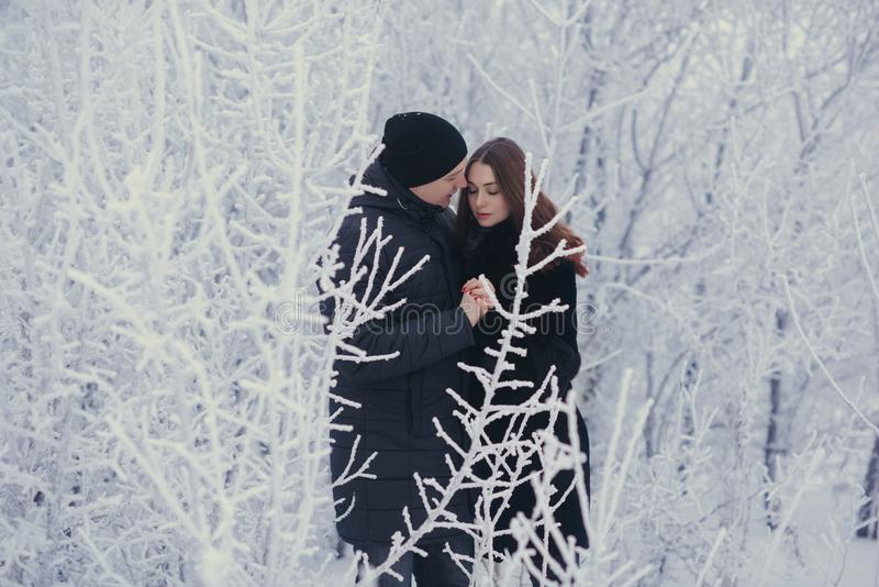 A loving couple on a winter walk. Snow love story, winter magic. Man and woman on the frosty street. The guy and the girl are rest royalty free stock images