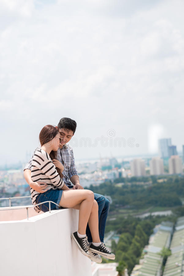 Loving couple. Young loving couple sitting on the edge of the roof and hugging stock photo