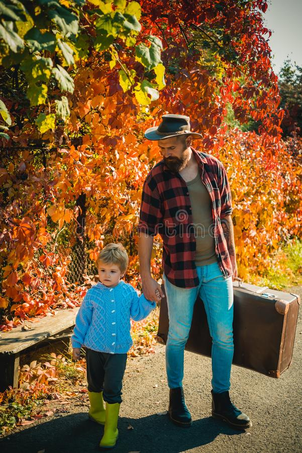Loving dad carefuly holds hand of his little son. Bearded father wearing hipster outfit and holding large vintage travel royalty free stock photos