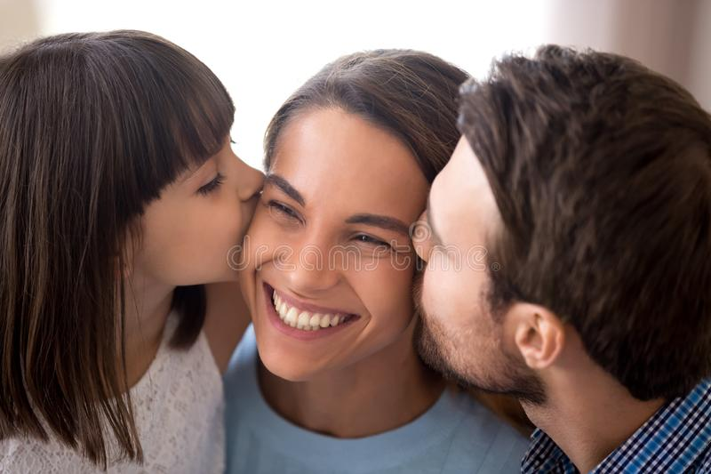 Loving dad and daughter kiss smiling mom on cheeks. Happy young mom kissed on cheeks by husband and daughter, cute preschooler girl with dad kiss smiling excited stock image