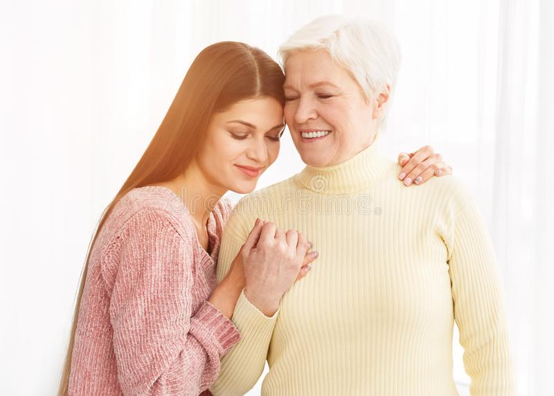 Loving daughter embracing mother, posing for family photo royalty free stock images