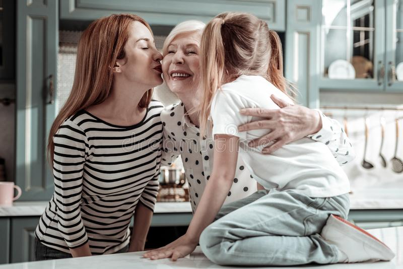Loving daughter and granddaughter kissing granny and showing their love stock photography