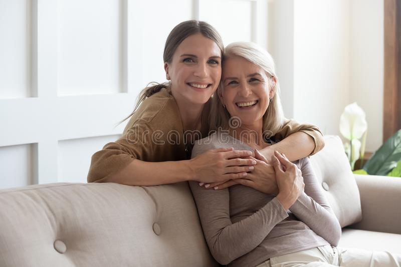Loving daughter hug mother people posing looking at camera. Loving adult 30s daughter hug elderly mother from behind while mom sitting on couch people posing royalty free stock photography