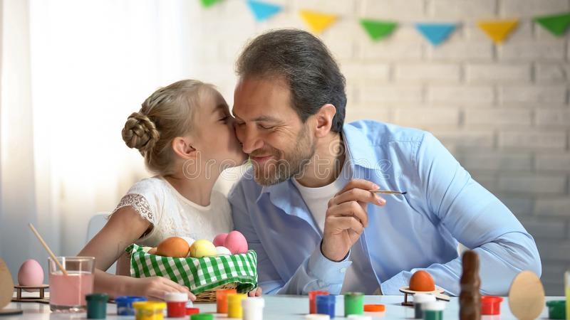 Loving daughter kissing father on cheek, painting eggs for Easter festival royalty free stock image