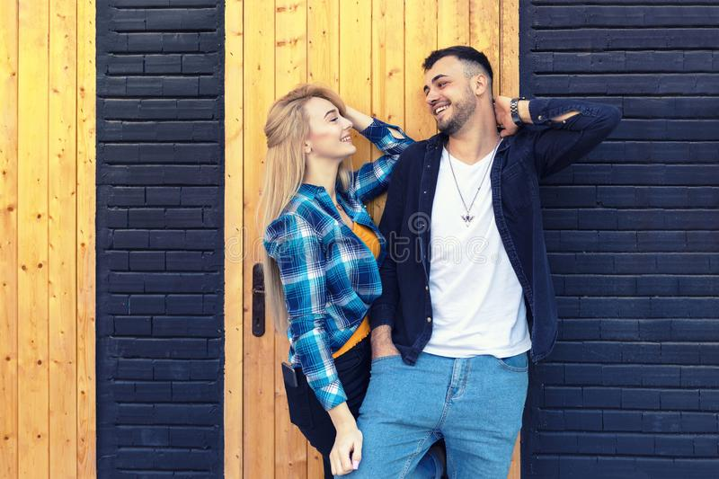 Loving diverse young couple in love  on wall looking at each other dreaming about their future together stock images