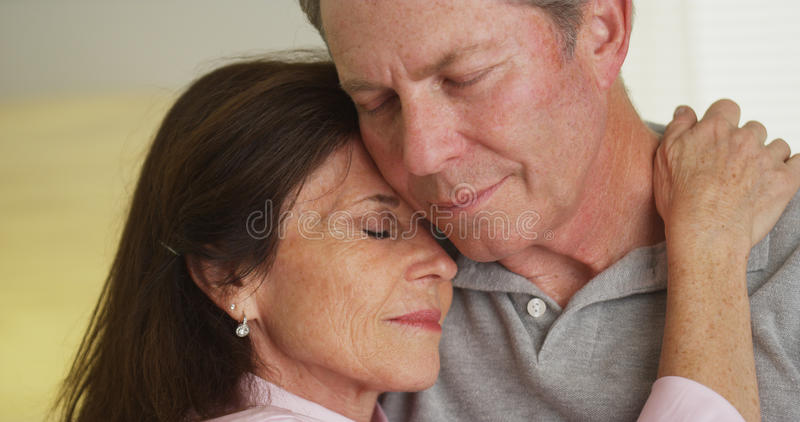 Loving elderly couple holding each other royalty free stock image