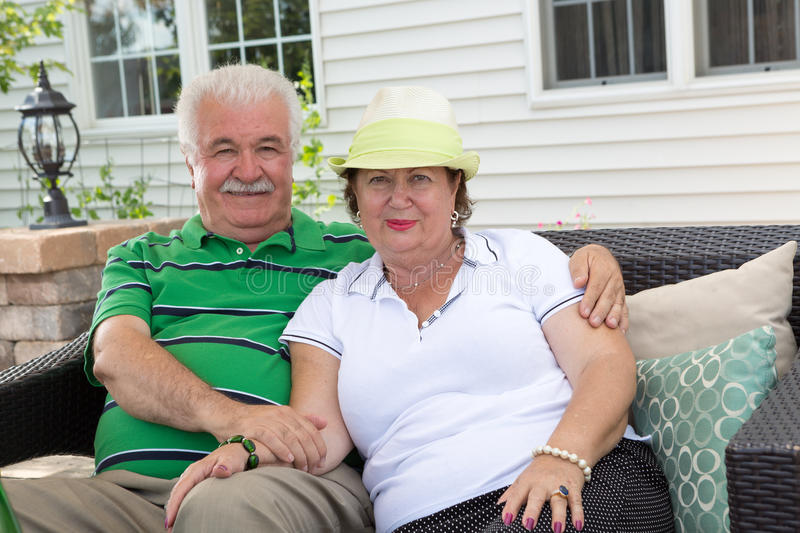 Loving elderly couple relaxing on an outdoor patio. Affectionate elderly couple relaxing on an outdoor patio sitting arm in arm on a garden sofa in front of stock images