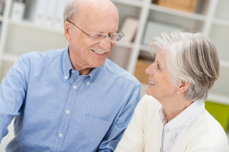 Loving elderly couple smiling at each other royalty free stock images
