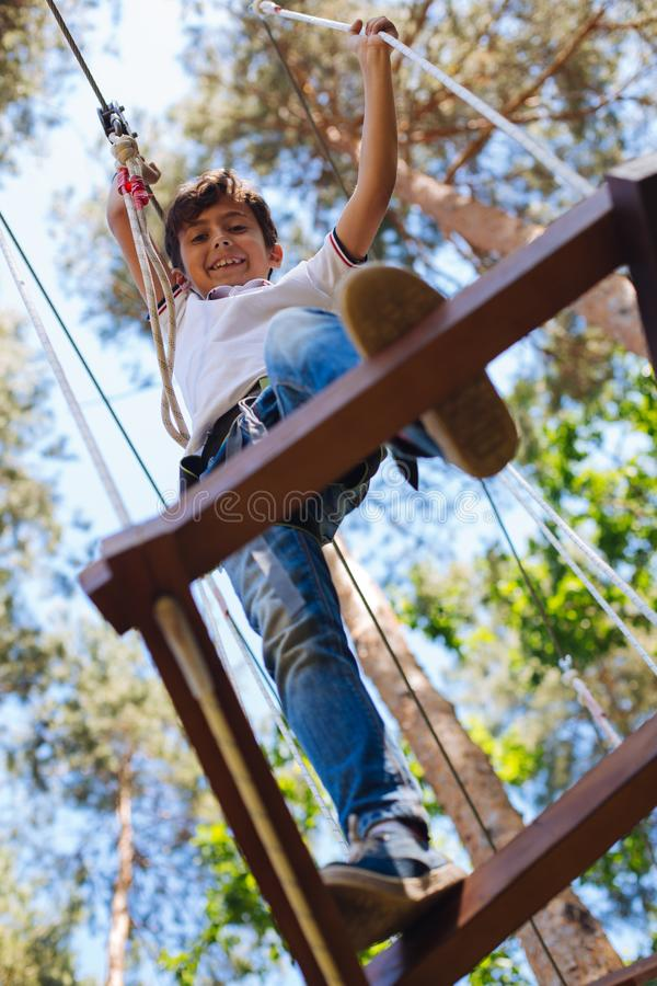Cheerful preteen boy making step while climbing at rope park stock photo