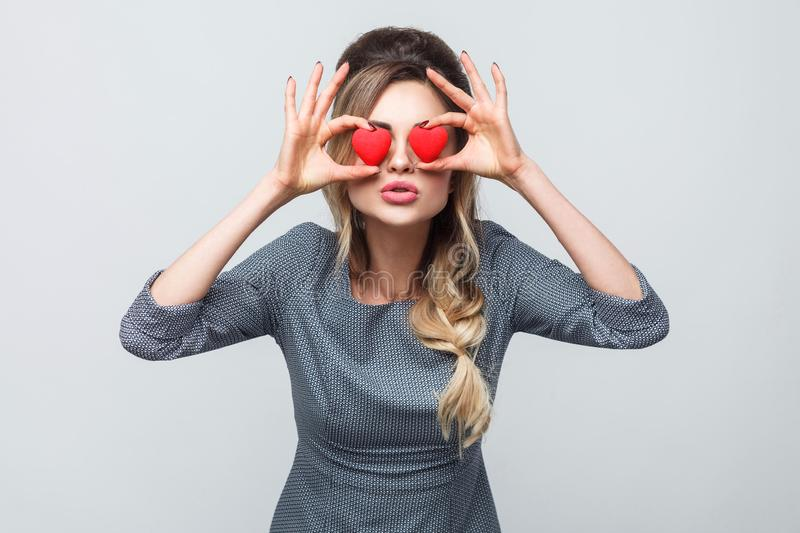 Loving eyes. Beautiful romantic caucasian young woman holding two valentine hearts in front of her eyes like glasses while royalty free stock images