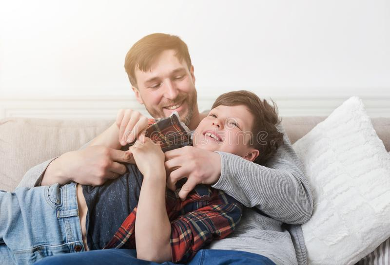 Loving father having fun with his son on sofa stock photos
