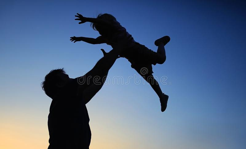 Loving father and his little son having fan together outdoors. Family as silhouette on sunset royalty free stock photography