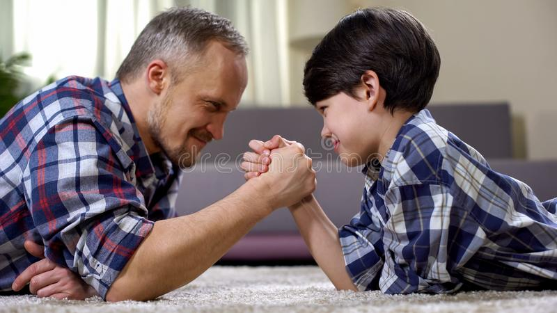 Loving father and kid arm wrestling on the floor, weekend leisure at home, fun royalty free stock photography