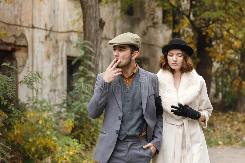 Loving gangsters retro couple is walking around old building. The guy smokes cigar while the girl looks down. Outdoors. stock image