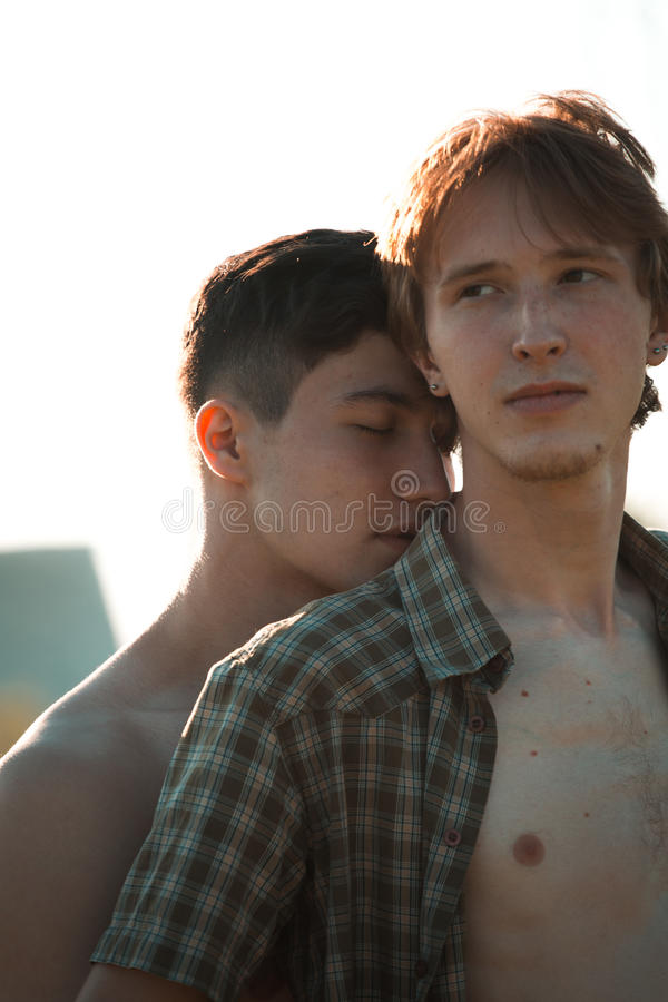 Loving gay couple. In field stock image