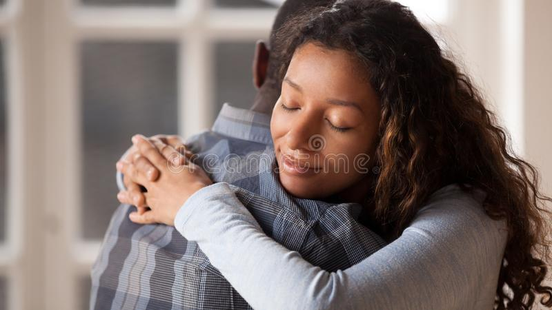 Loving girlfriend hug boyfriend happy to reconcile after fight. Happy mixed race women hug black men husband glad to make peace after fight, loving young stock image