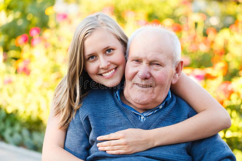 Loving granddaugher. Beautiful granddaughter visiting her elderly kind grandfather stock images