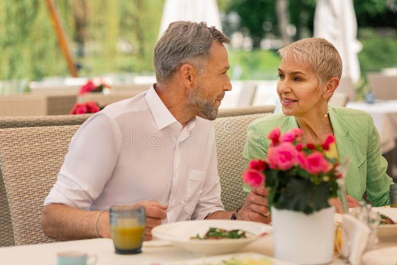 Loving grey-haired mature man looking at his beautiful wife stock images
