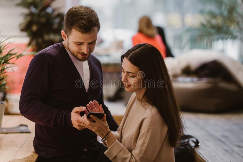 Loving guy and girl dressed in sweaters and jeans sit at the table in the cafe and looks at the mobile phone royalty free stock images