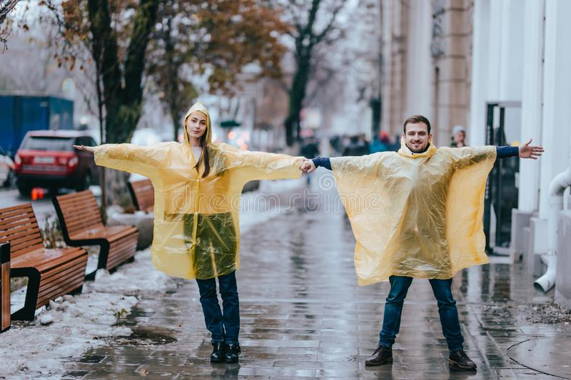 Loving guy and girl dressed in yellow raincoats stand on the street in the rain stock images