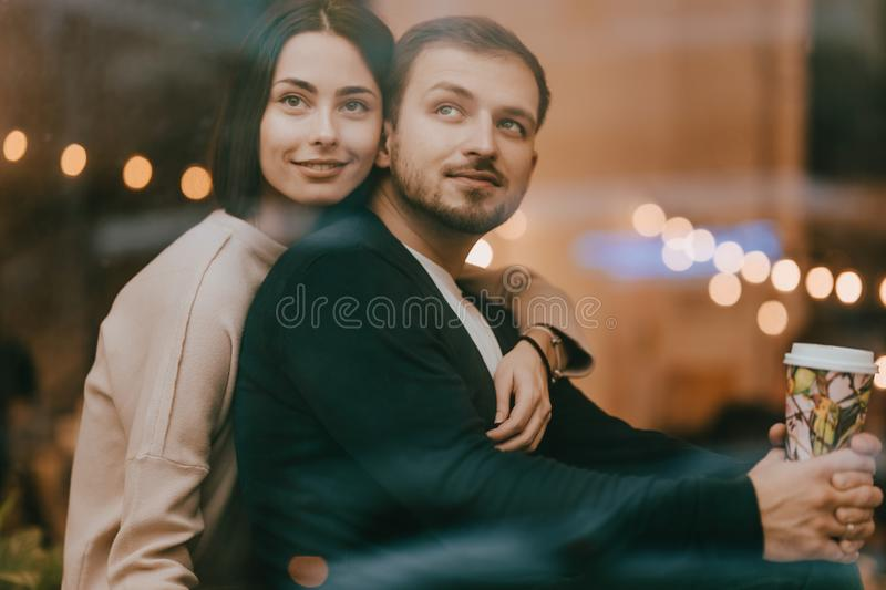 Loving guy and girl sit hugging on the windowsill in a romantic cafe stock image