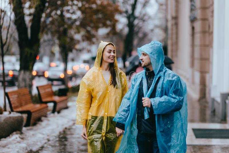 Loving guy and girl in the yellow and blue  raincoats stand on the street in the rain royalty free stock photos