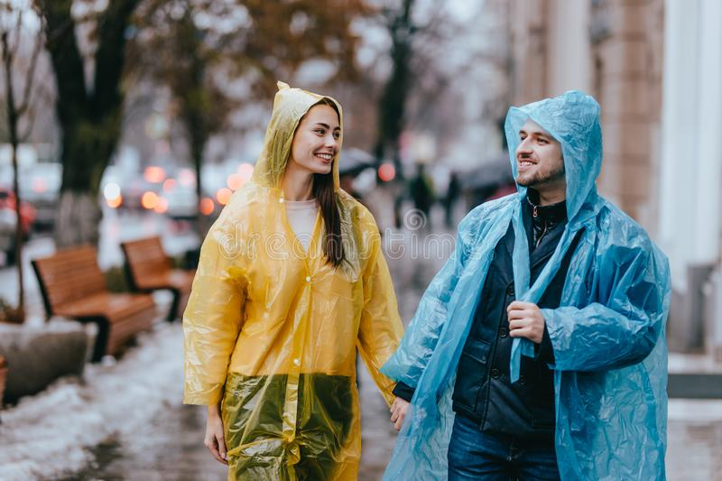 Loving guy and girl in the yellow and blue  raincoats walk on the street in the rain royalty free stock photography