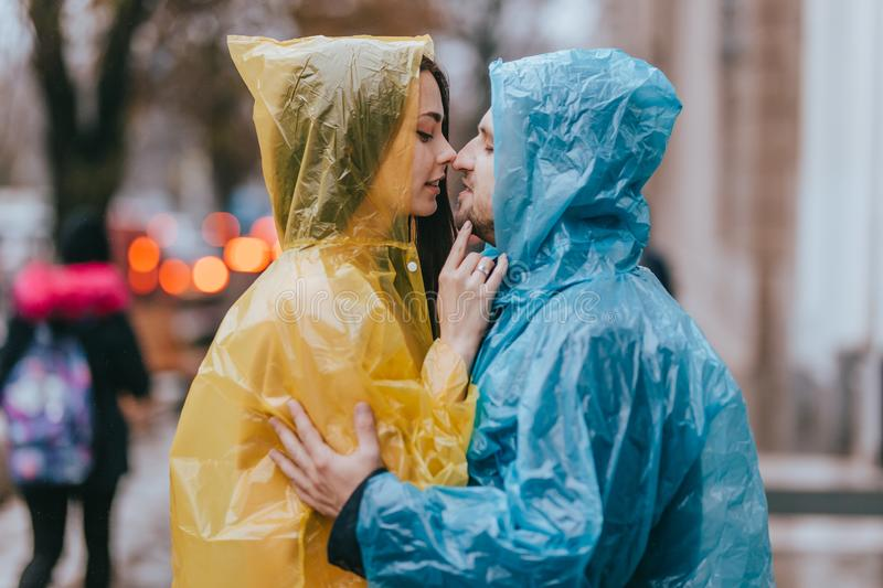 Loving guy and his girlfriend in the raincoats stand face to face on the street in the rain royalty free stock image