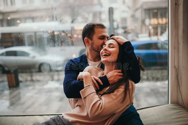 Loving guy hugs his beautiful happy girlfriend sitting on the windowsill in a cozy cafe. royalty free stock images