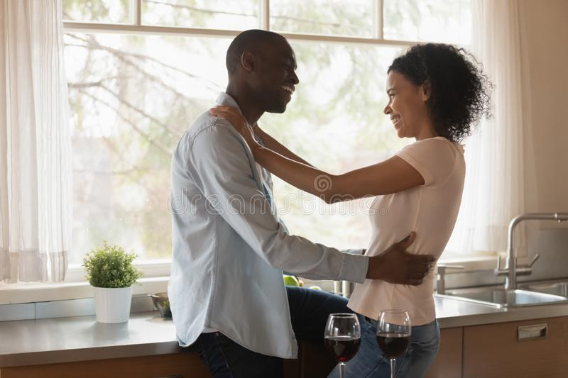 Loving african American couple hug enjoying time together. Loving happy african American husband and wife hug cuddle in kitchen enjoy romantic date at home stock photos
