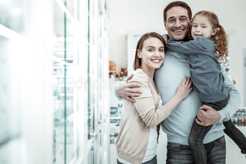 Loving happy family choosing the vitamins in the drugstore. Buying medicine. Loving happy family choosing the vitamins in the drugstore stock photography