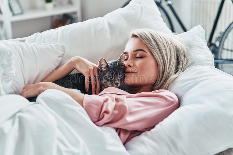 Loving her cat. Attractive young woman holding her cat and smiling while lying in bed at home stock images